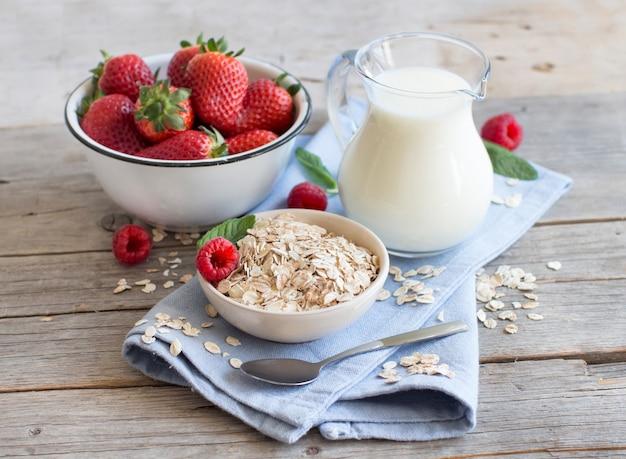 Овсяные хлопья в миске с ягодами и молоком на дереве крупным планом