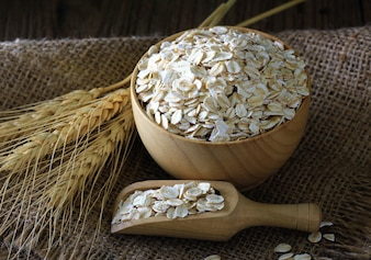 Rolled oats  in a wooden bowl on a sack