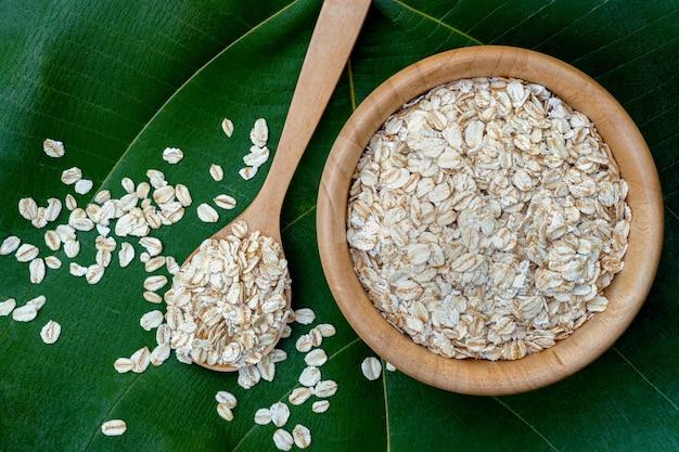 緑の葉の上に木製のカップとスプーンでロールドオーツ、上面図。健康的な全粒穀物食品です。