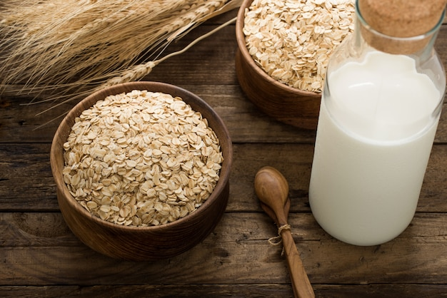 Rolled oats, oats in bowl and jug of milk on wooden background