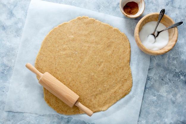 Раскатанный пирог или печенье размякли на бумаге для выпечки. вид сверху.
