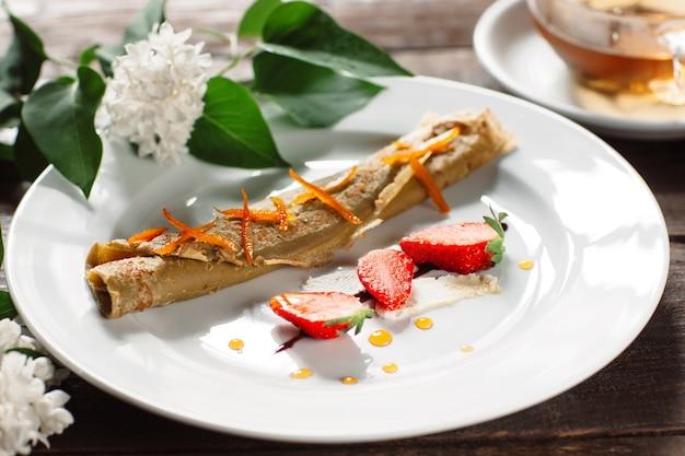 흰색 접시에 딸기와 압 연된 팬케이크