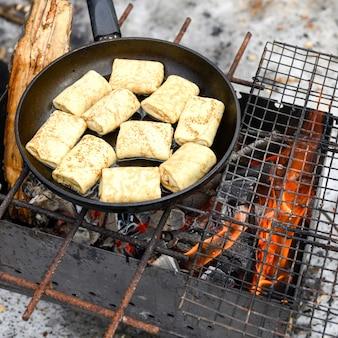 채우는 롤 팬케이크는 그릴에서 불에 프라이팬에 튀겨집니다.
