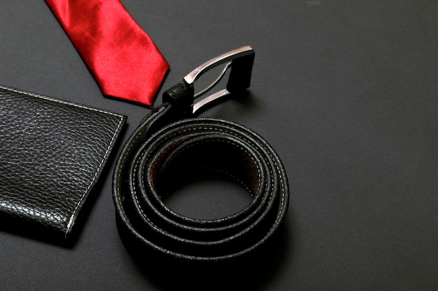 Rolled red men's tie and a leather belt