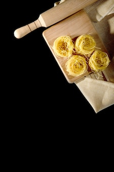 Rolled tagliatelle shape of italian pasta on black stone background . high quality photo.