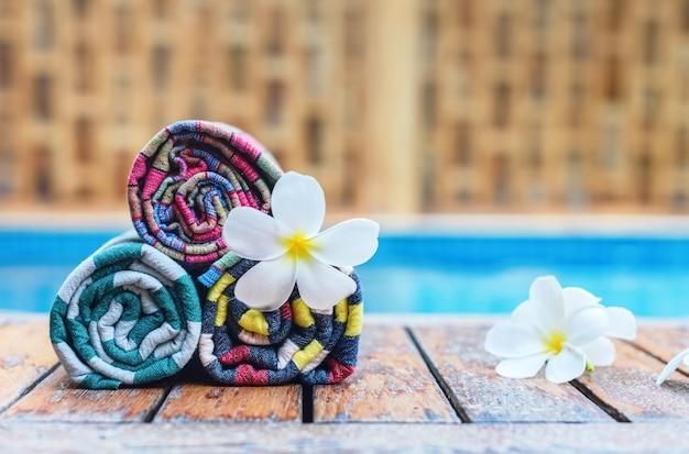 Свернутые полотенца и цветы плюмерии