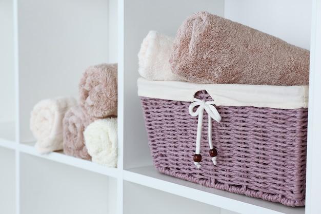 Свернутые полотенца с плетеной корзиной на полке стеллажа