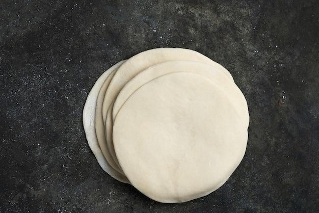 Раскатанное сырое тесто для индийских лепешек чапати. готовы приготовить концепцию. легкое питание. домашняя еда. плоский вид сверху