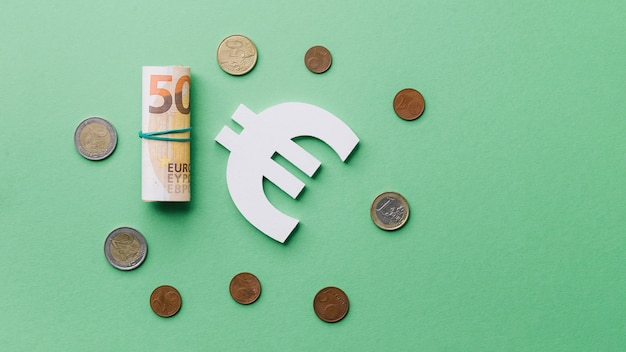 Rolled up banknote with coins and euro sign on green backdrop