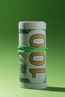 녹색 배경에 고립 된 지폐를 올리고