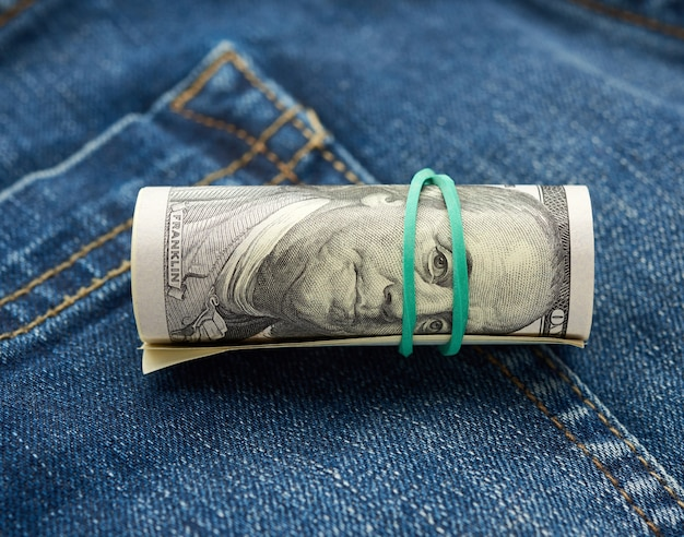 Rolled up dollar bills over jeans fabric