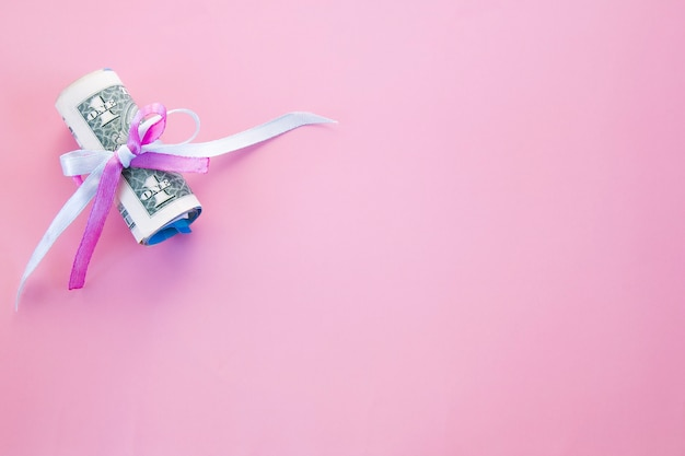 핑크에 복사 공간이 파란색과 분홍색 리본으로 보안 달러 지폐를 겹쳐서.