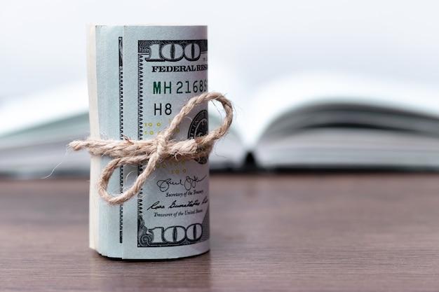 Свернутые доллары возле раскрытой книги