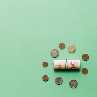 Rolled up euro bank note with coins on green backdrop