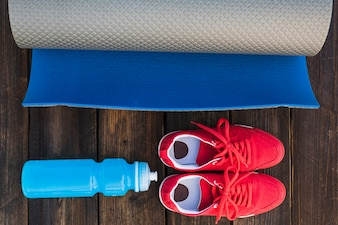Rolled up exercise mat with water bottle and pair of sport shoes on wooden table
