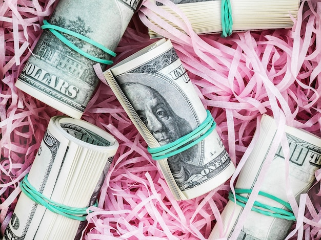 Rolled-up hundred-dollar bills lie in pink paper backing, close-up, top view