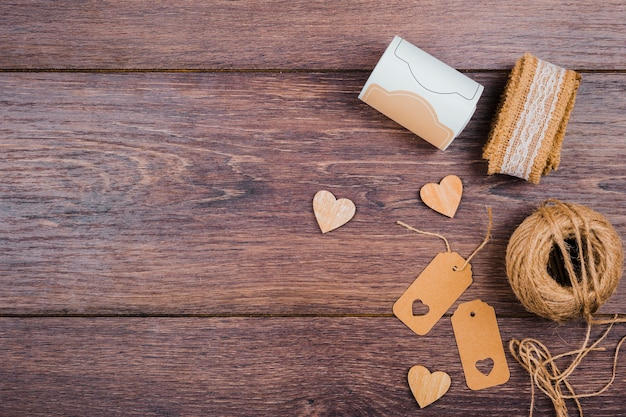Rolled up lace; wooden heart shape; tags and jute spool on wooden desk