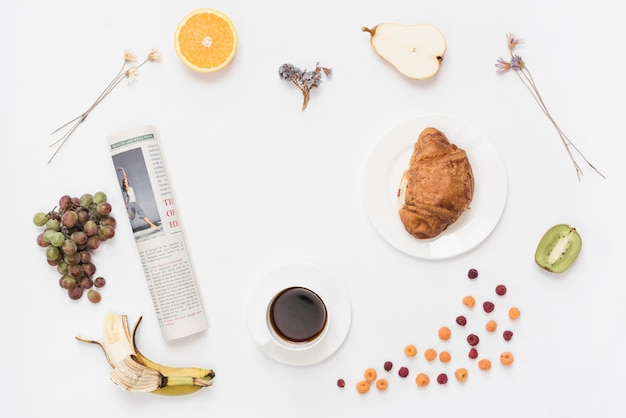 Rolled up newspaper with coffee cup; croissant and fruits on white background