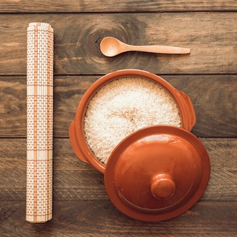 Rolled up place mat with rice in brown pot with lid and wooden spoon
