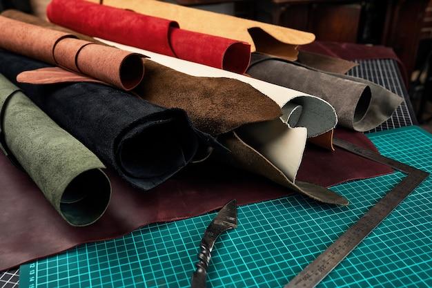 가죽 조각을 자르기위한 매트와 도구가있는 테이블에 가죽 배경에 다양한 색상의 정품 가죽 질감 샘플을 감았습니다.