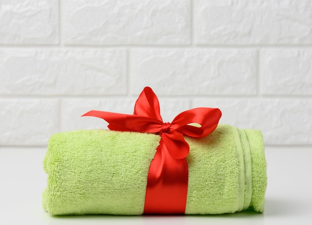 욕실의 흰색 선반에 빨간색 실크 리본으로 묶인 테리 녹색 수건을 말아서 닫습니다