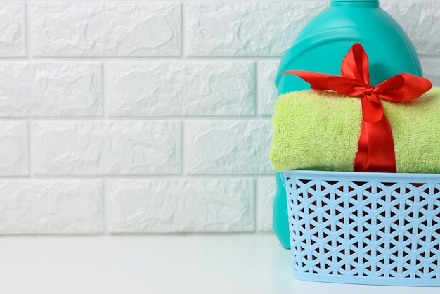 A rolled up terry green towel tied with a red silk ribbon and a plastic bottle of liquid laundry powder on a white shelf in the bathroom