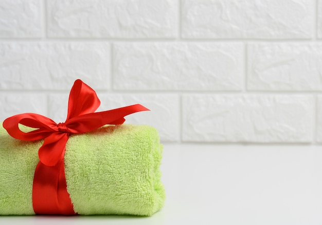 Rolled up terry green towel tied with red silk ribbon on white shelf in bathroom, copy space