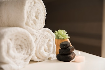 Rolled up towel with spa stone and illuminated candle on table