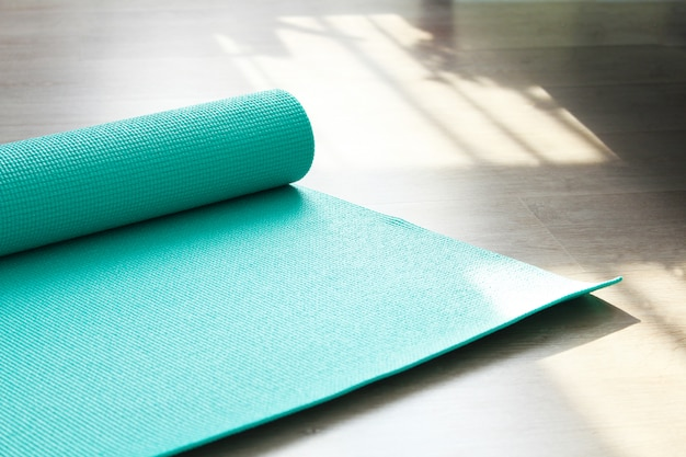 Rolled up yoga or pilates mat for exercise on natural wooden floor, sport class