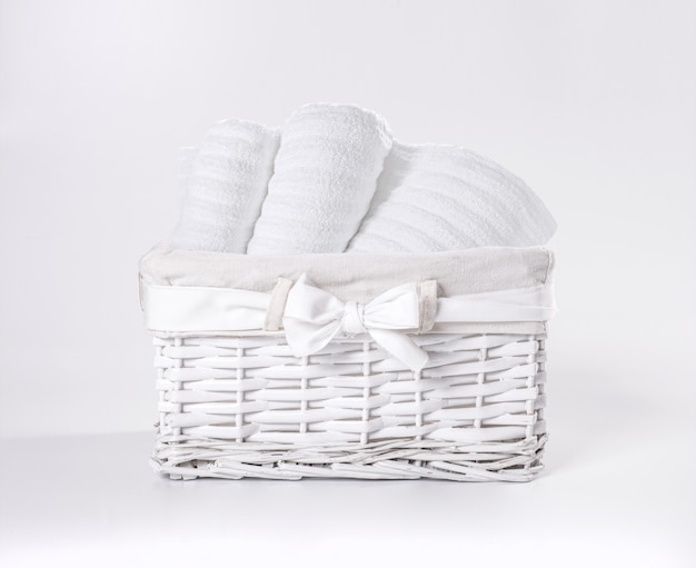 Rolled white soft terry towels in the basket against a white backdrop. striped towels in a white basket in front of a white backdrop.