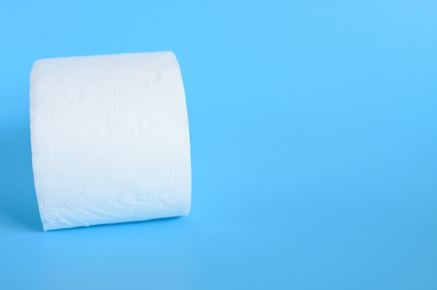 Rolled white toilet paper in a blue background. space for text