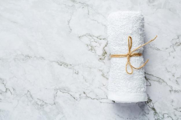 Asciugamano bianco arrotolato per il trattamento termale messo sul pavimento in marmo bianco
