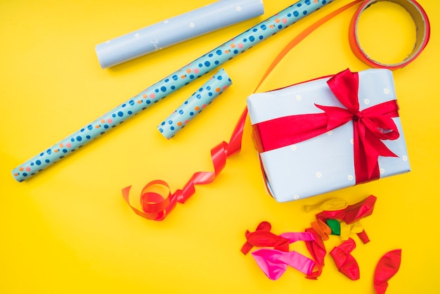 Rolledup gift paper; red ribbon; deflated balloons and present on yellow background