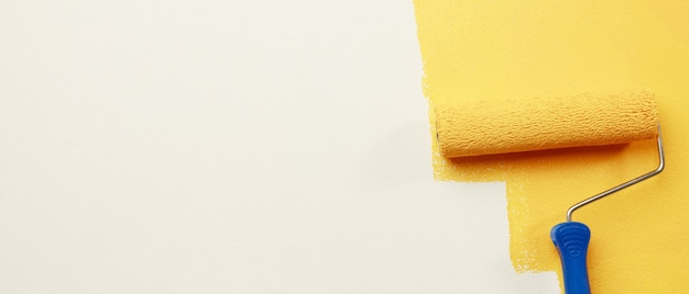 Роликовая кисть, рабочий рисует на поверхности. покраска стен. квартира, ремонт краской желтого цвета.
