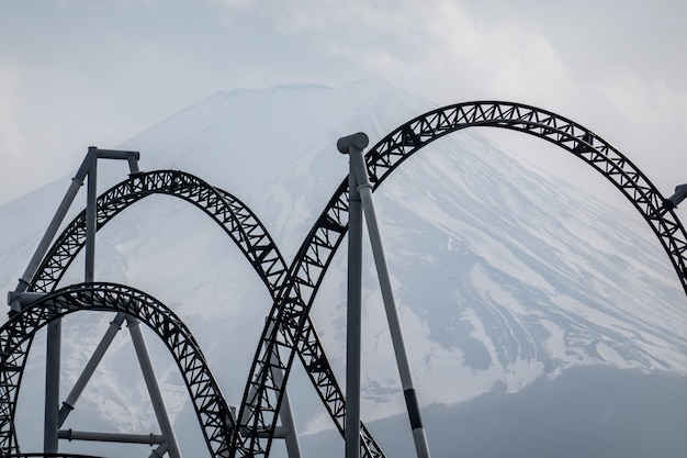 Roller coaster railqay track with view of mt. fuji or fuji-san, japan.