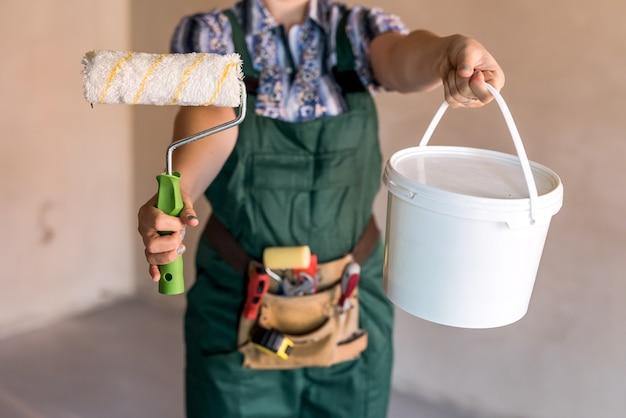 塗装用ローラーと女性の手でバケツをクローズアップ