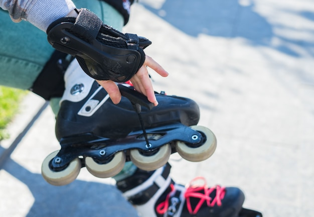 Roller girl unscrewing wheels on roller skates with allen key