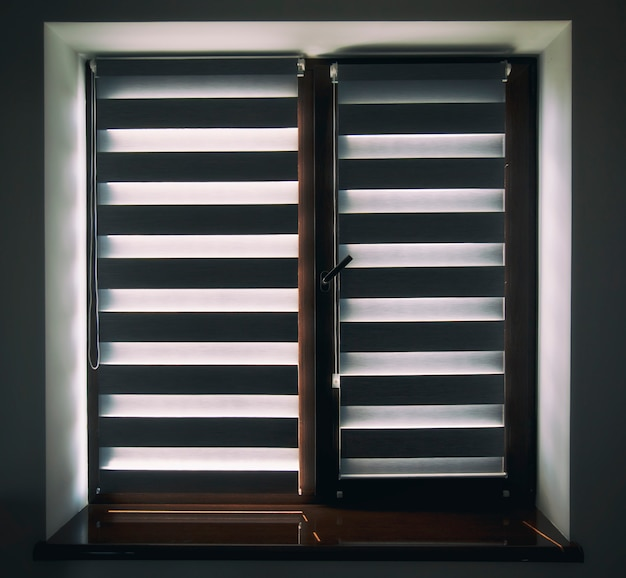 Roller shutters on the plastic brown window in the living room