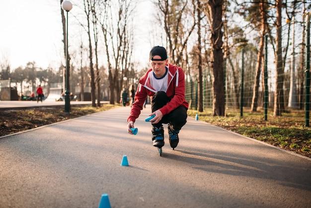 ローラースケートでスケートをする人、都市公園の歩道でバランス運動。男性のローラースケーターレジャー