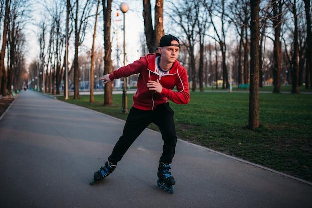 ローラースケート選手は、都市公園の歩道で乗ります。男性ローラースケートレジャー