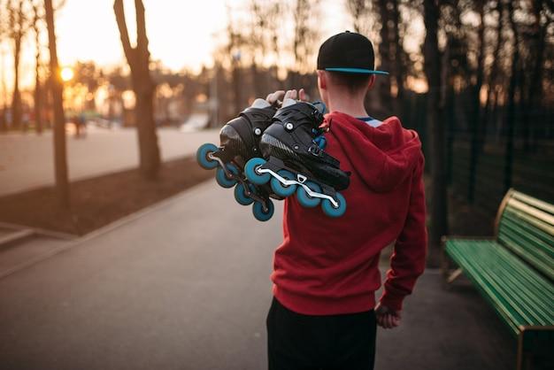 都市公園の歩道、背面図で手にスケートを持ったローラースケート選手。男性ローラースケートレジャー