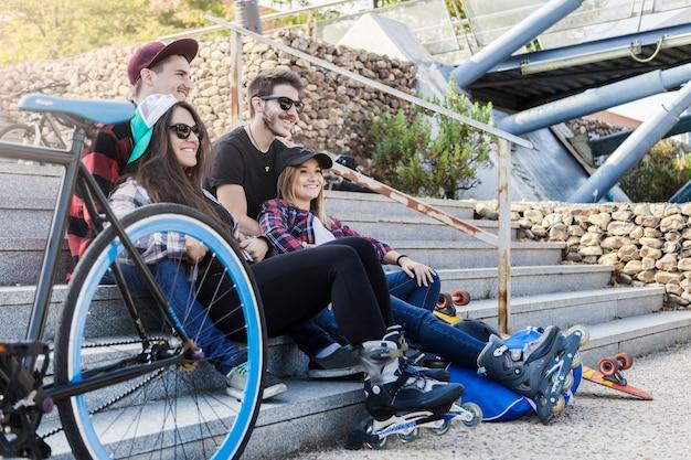 Pattinatori a rotelle che riposano vicino alla bicicletta