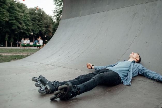 ローラースケート、スロープに横たわっている男性スケーター。