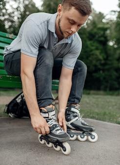 Roller skating, male skater puts on skates in park. urban roller-skating, active extreme sport outdoors, youth leisure, rollerskating