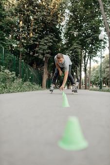 ローラースケート、男性スケーターはコーンを公園に置きます。