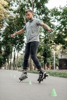 ローラー スケート、公園のコーンの周りを転がる男性スケーター。アーバンローラースケート、アウトドアでのアクティブなエクストリームスポーツ、若者のレジャー、ローラースケート