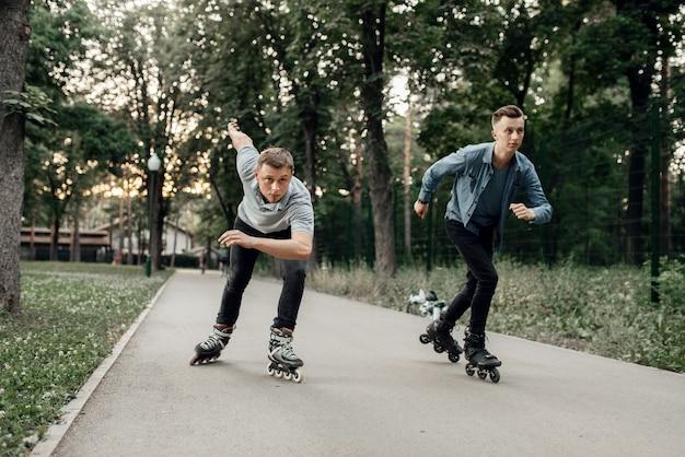 Roller skating, two male skaters begins speed race in summer park. urban roller-skating, active extreme sport outdoors, rollerskating