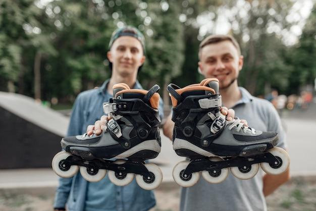 ローラースケート、2人の男性スケーターがスケートを手に持っています。アーバンローラースケート、アウトドアでのアクティブなエクストリームスポーツ、ローラースケート