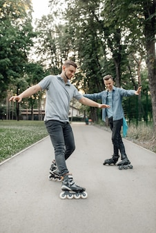 Roller skating, two male skaters rolling in summer park. urban roller-skating, active extreme sport outdoors, rollerskating