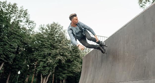 ローラースケート、ランプから転がる若い男性スケーター。アーバンローラースケート、アウトドアでアクティブなエクストリームスポーツ